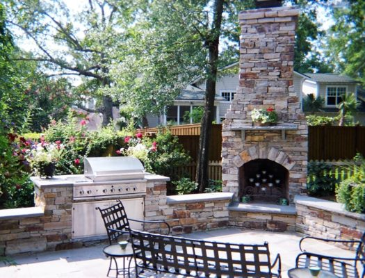 outdoor room featuring stone patio and fireplace, built in grill and seating wall in garden