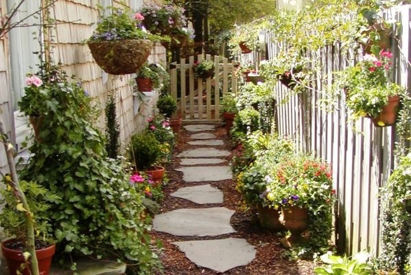 stepping stone pathway in a side garden with potted plants, wooden fence and a wooden gate
