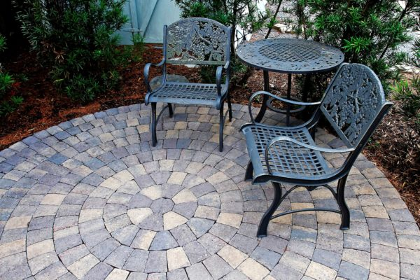 round stone pavers circle kit patio with ironwork table and chairs in garden