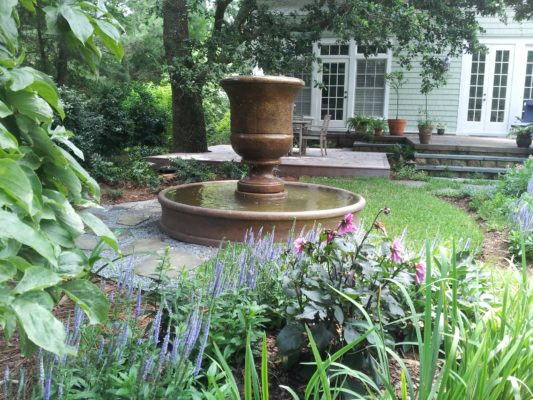 large stone urn fountain bubbling water into a round pool in a lush backyard garden