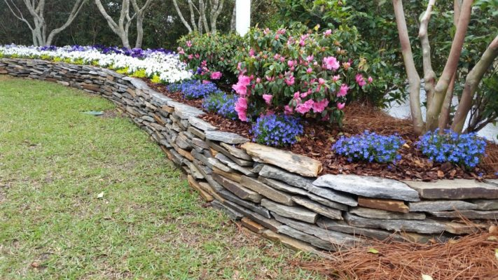 stacked stone retaining wall in garden with colorful flowers