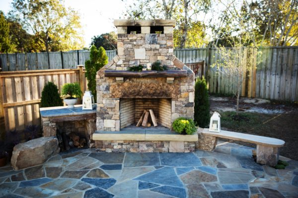 stone outdoor fireplace on flagstone patio with stone bench