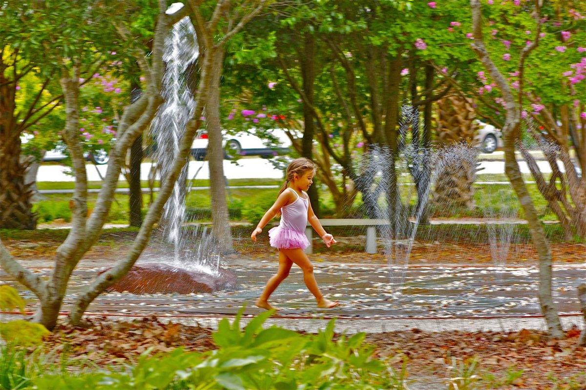 girl in pink tutu playing in water fountain playground at a park amongst flowering trees