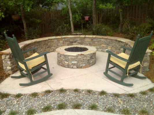 round stone fire pit and seating wall on patio with rocking chairs in garden