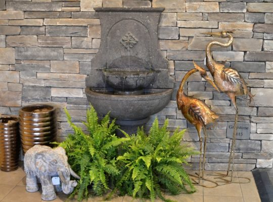 stone wall fountain, ceramic pots, and garden art by a stone wall in the showroom