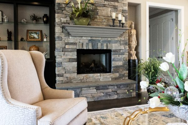 stone fireplace with raised bluestone hearth topped with wooden mantel in a living room