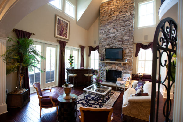 stone wall fireplace with raised hearth, stone mantel and TV in a two-storey living room
