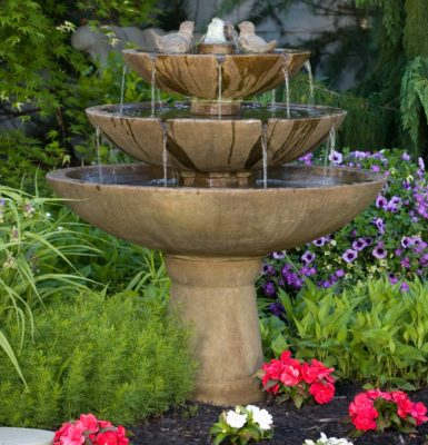 three-tiered stone tranquility fountain with sculpture birds in garden of flowers