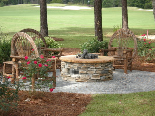 round stone gas firepit on a round patio with willow wooden furniture in a garden by a golf course