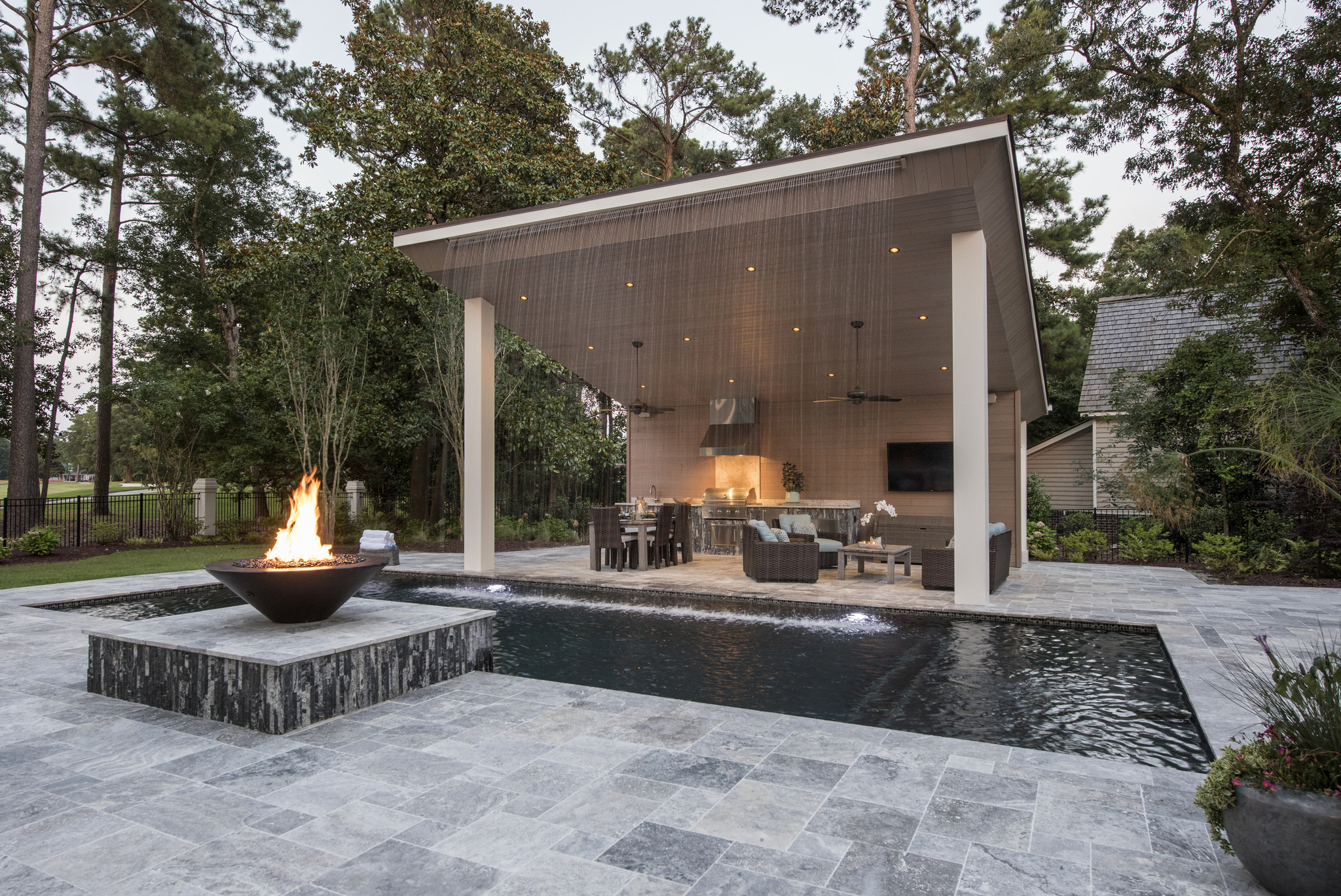 outdoor kitchen and living room featuring fire bowl on stone patio and waterfall feature