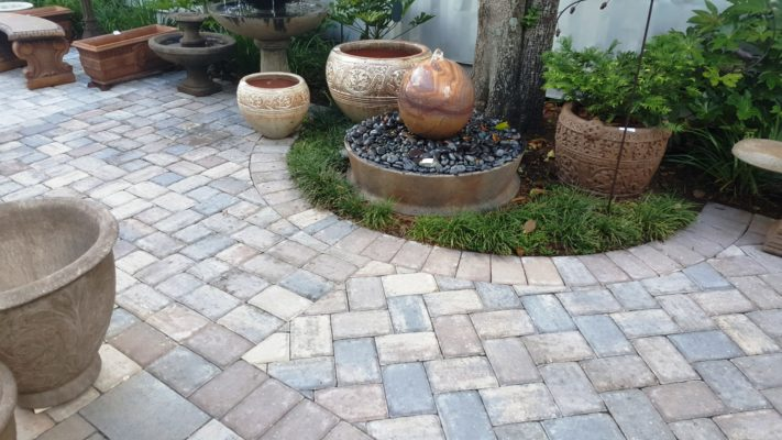 stone pavers patio, fountain, bench, and plant pot at stone garden display