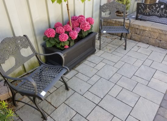 stone pavers patio, stone wall, chairs, and plant pot at stone garden display