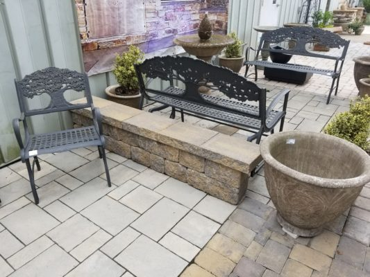 stone pavers patio, stone wall, fountain, bench, chair and plant pot at stone garden display