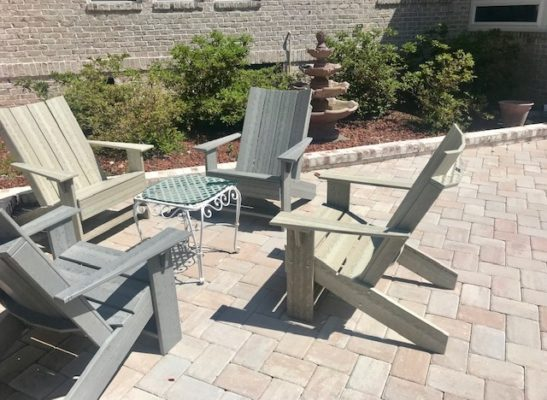 stone pavers patio with wooden chairs in garden with fountain