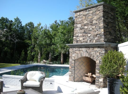 outdoor living room featuring stone patio, stone fireplace and swimming pool