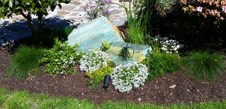 large turquoise green stone boulder in a garden with flowers