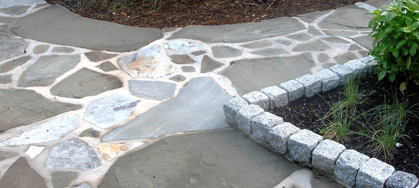 flagstone pathway with granite boulder block edges by a garden