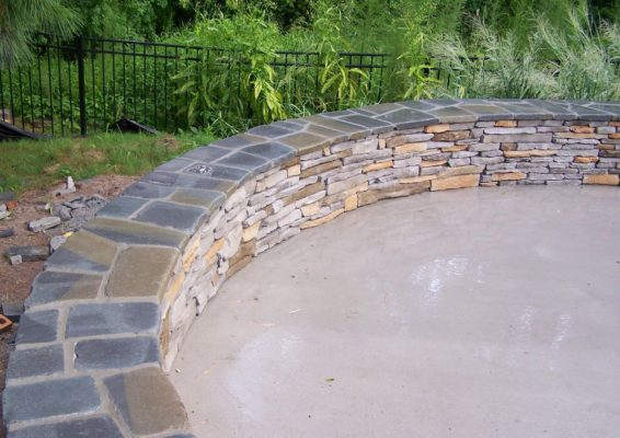 round stone seating wall in a garden