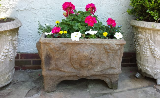 stone garden planter with colorful flowers