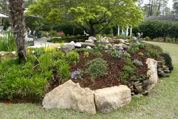 large, cream-colored, stone boulders create a mulch filled garden with plants and flowers