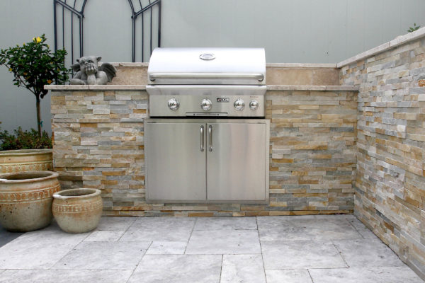 stone, outdoor living kitchen, grill cabinet with garden art and plant pots on a stone patio at stone garden display