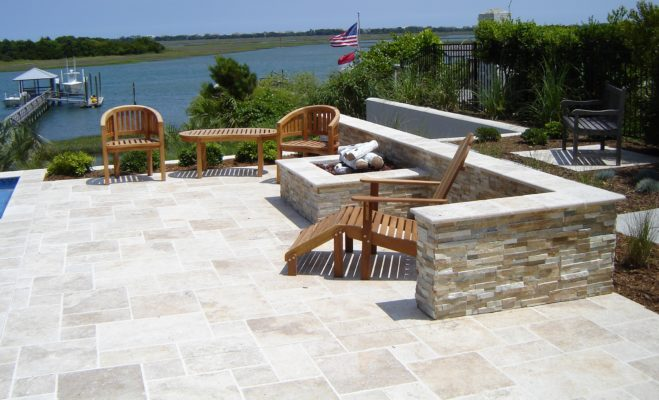 stone outdoor living patio with square fire-pit and seating wall overlooking waterway