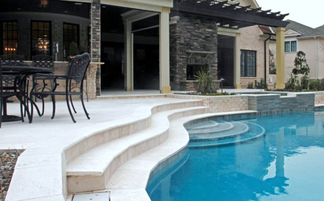 outdoor living room featuring travertine stone steps leading into a swimming pool