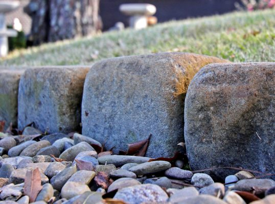 cobblestone edges a stone garden by a grassy area