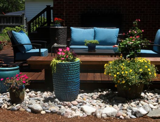ceramic pots with flowers nestle in a river stone garden to create an outdoor living area
