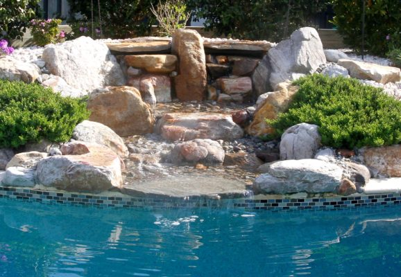 large, stone boulders form a garden fountain into a swimming pool