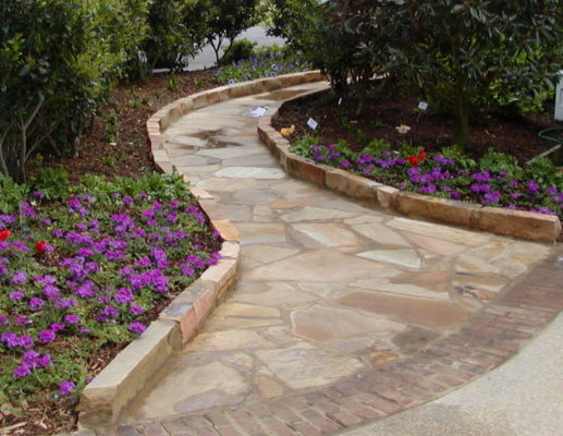 stone blocks edge a flagstone pathway through a garden of purple flowers and green trees