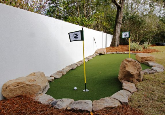 stone boulders in a backyard garden form a putting green