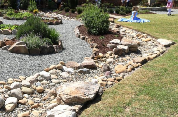 stones form a dry creek bed in a garden by gravel pathways
