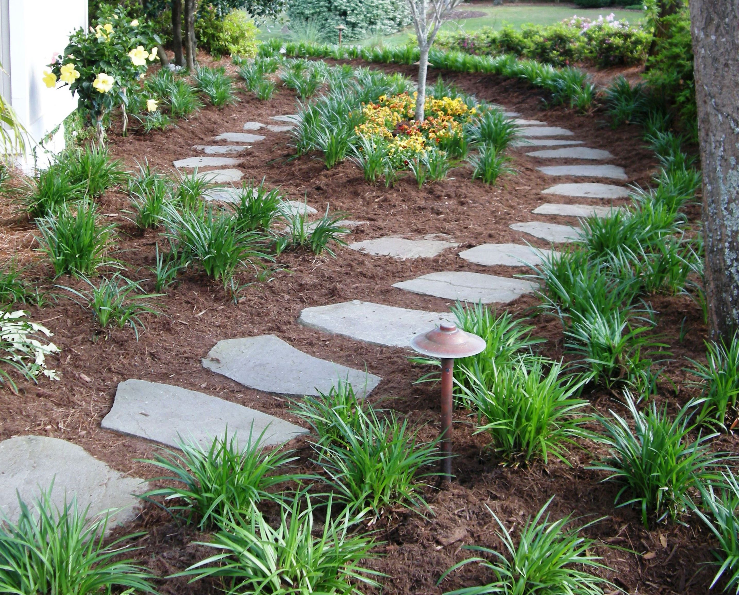 stepping stone garden pathway nestled in fresh mulch with flowers and foliage