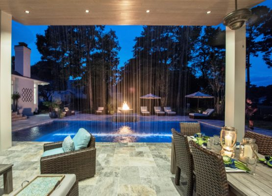 outdoor living and dining room featuring fire bowl and waterfall feature on a stone patio