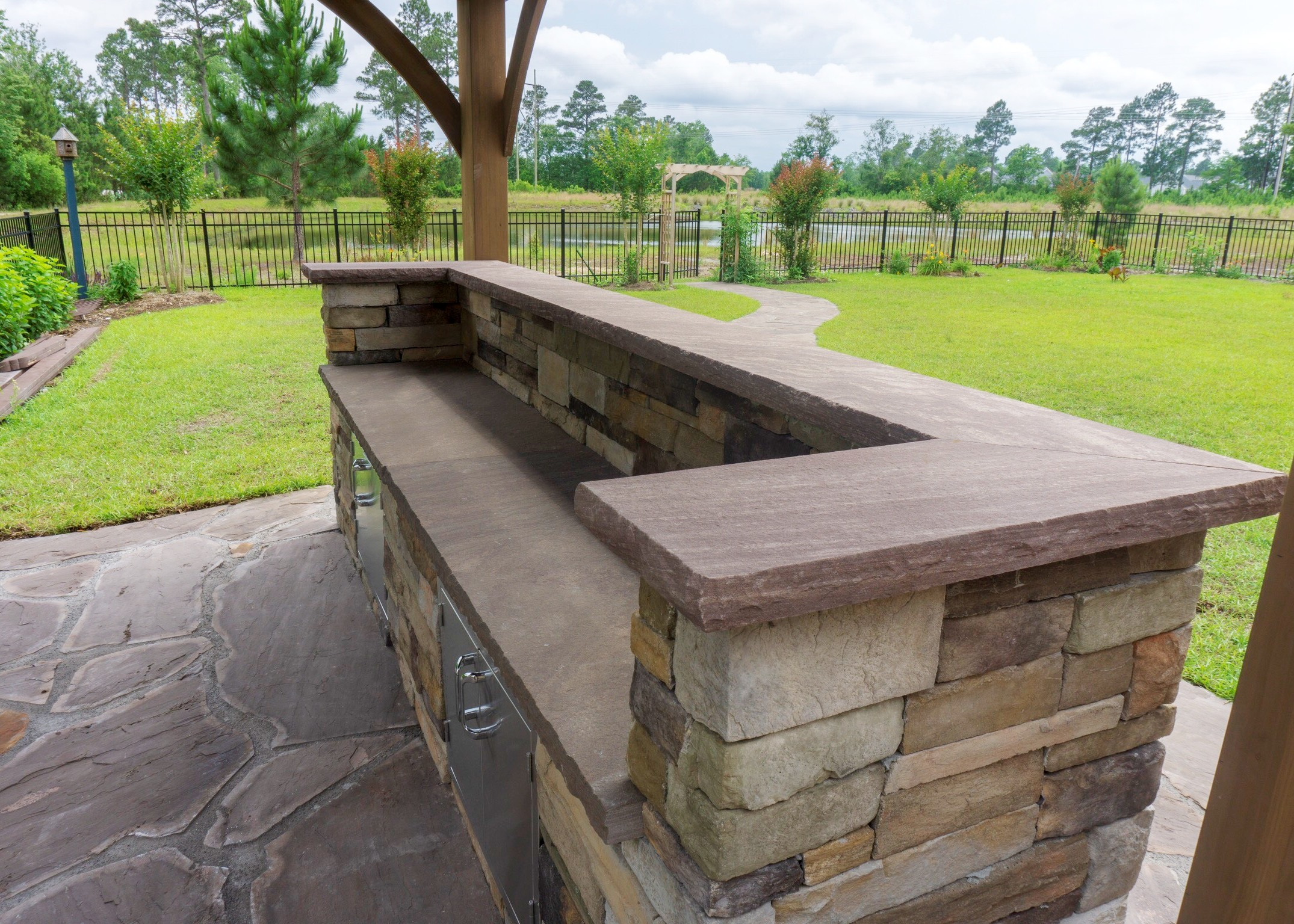 stone bar grill cabinet in a backyard garden for outdoor living