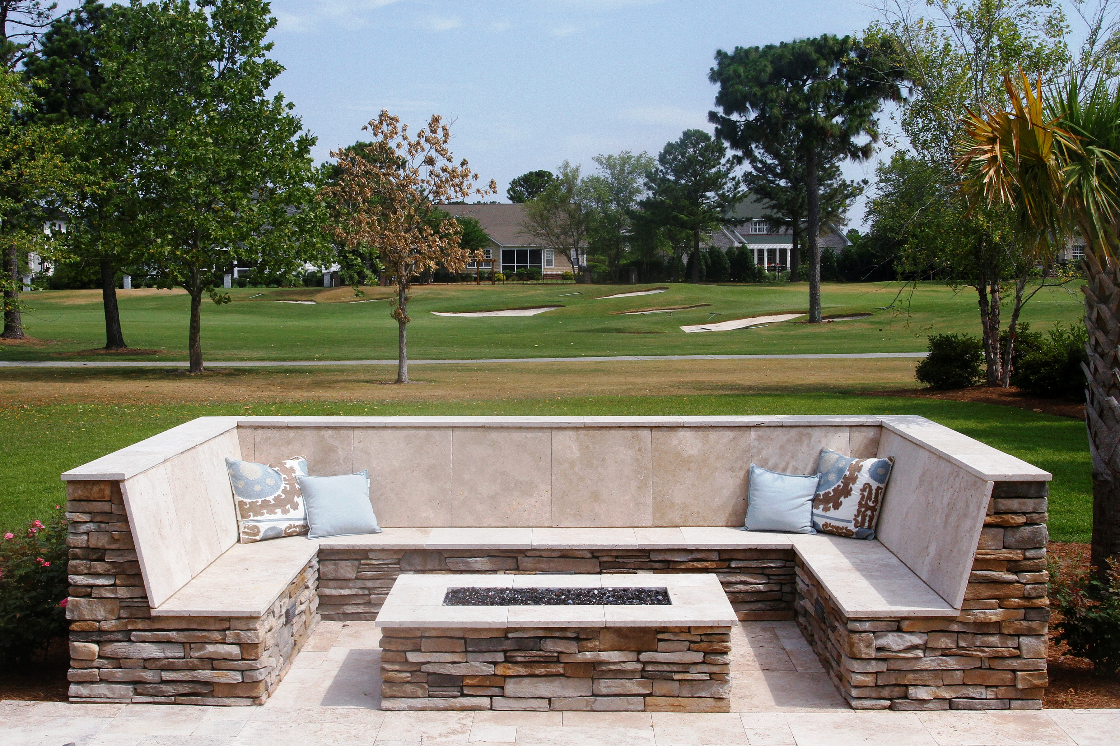 stone outdoor living patio with oblong fire-pit and seating bench overlooking golf course