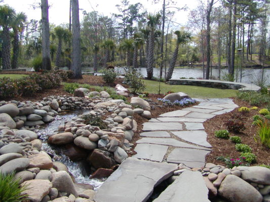 stone garden pond and fountain, flagstone bridge and pathway, leading to a stone seating wall and green lawn area overlooking a waterway
