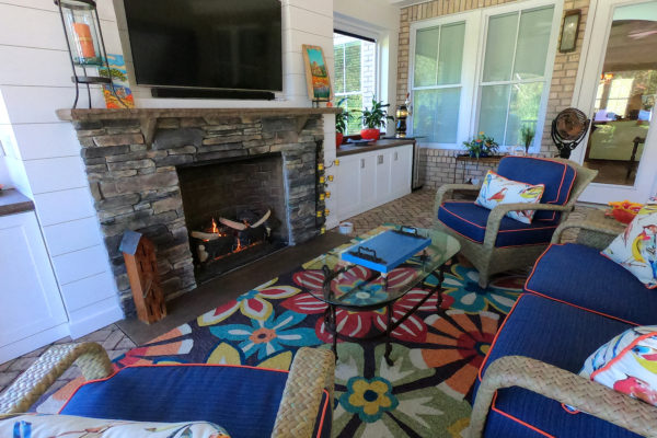 stone fireplace and outdoor living room in a sunroom with paver patio floor