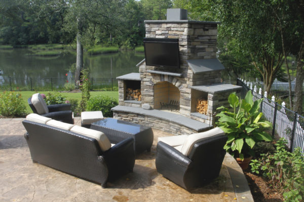 outdoor living room featuring a stone fireplace with television on a patio overlooking a pond
