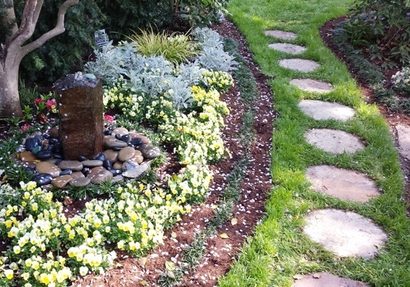 stone garden fountain bubbling water onto a bed of mexican beach pebbles by a stepping stone pathway in a garden