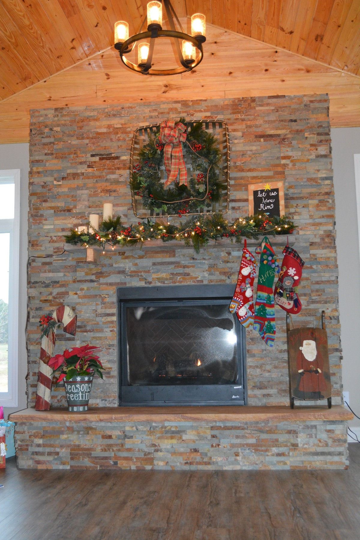 stone fireplace with raised hearth decorated for Christmas