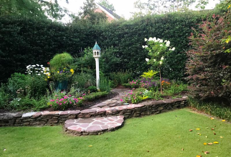 stone garden pathway and edging with bird feeder by hedge