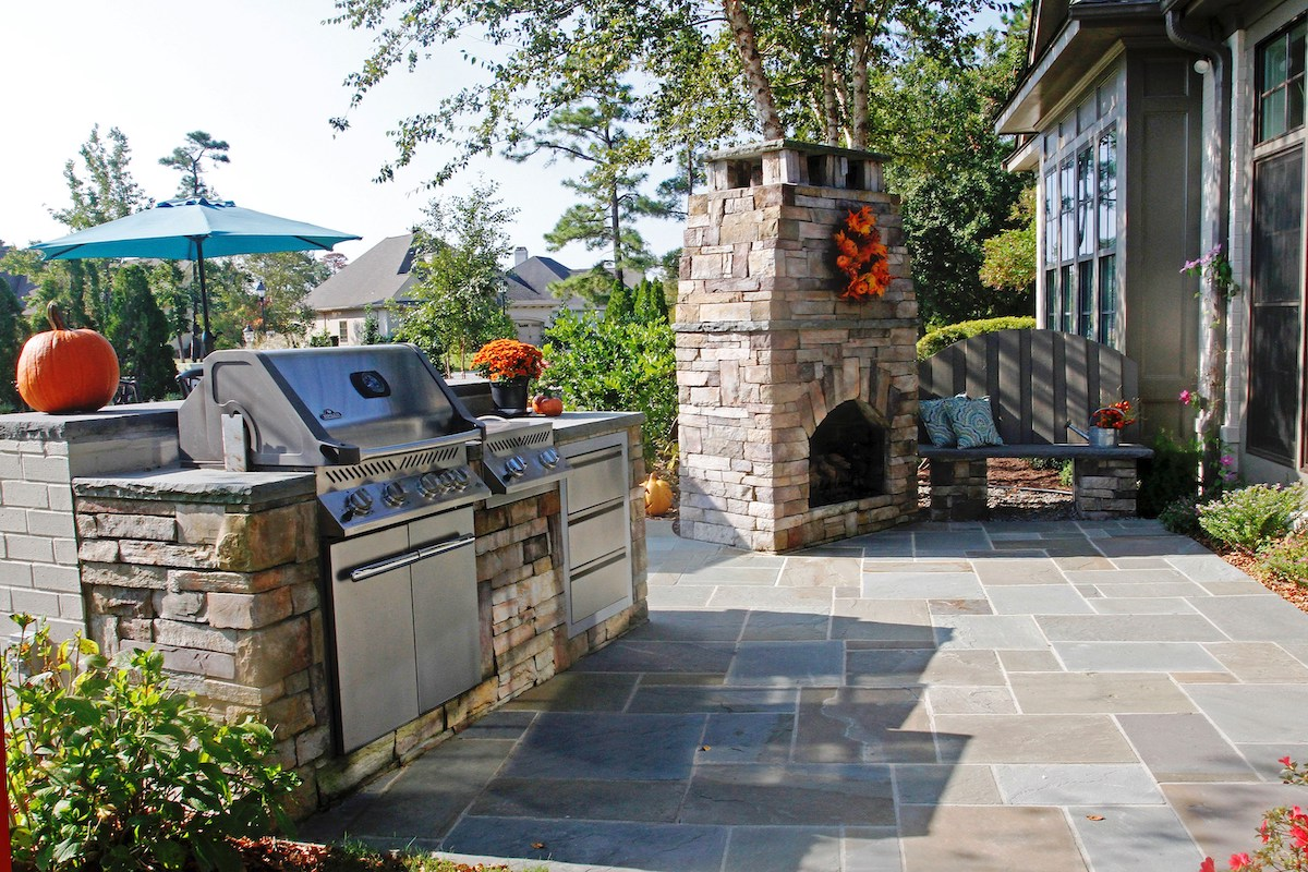 stone garden patio, fireplace and grill station decorated for Fall