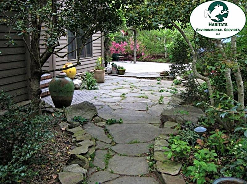 stone pathway and patio nestled in trees in a backyard garden