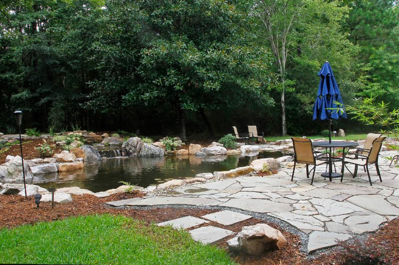 waterfall pond in a stone garden patio with seating by large trees