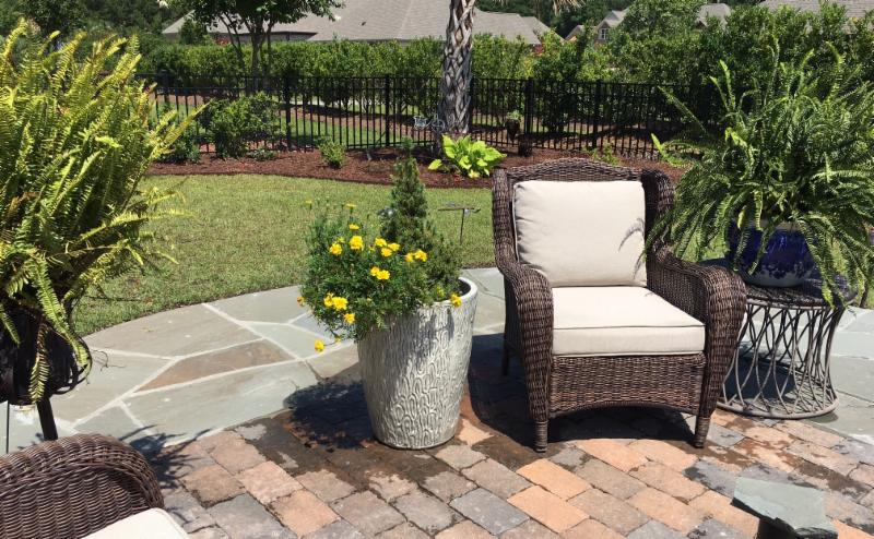 natural stone and brick patio in backyard garden with chair