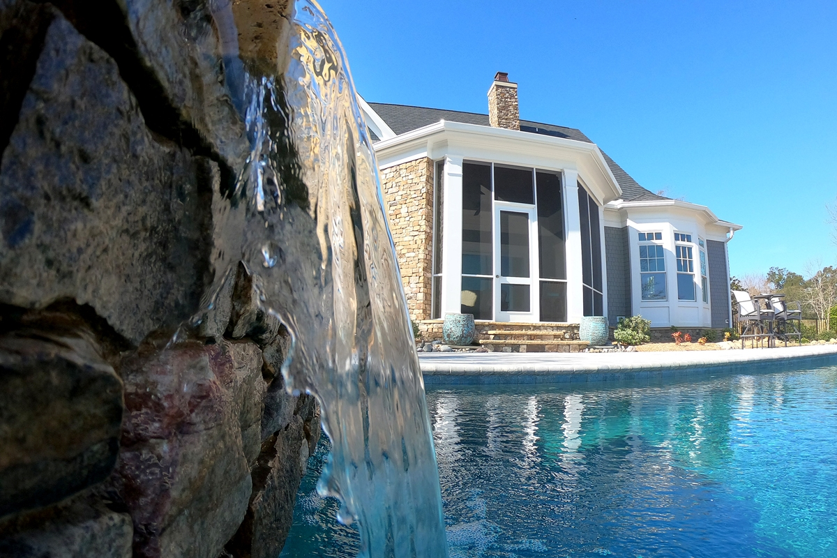 fountain water falling into a backyard swimming pool by a screened in porch with stone veneer exterior wall