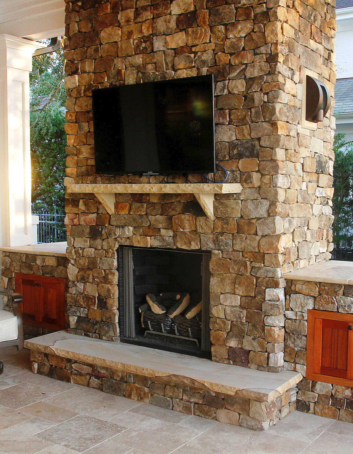 stone fireplace with raised hearth and side cabinets with TV mounted over a stone mantel in a sunroom
