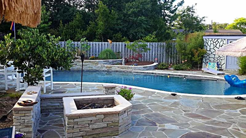 stone back yard garden with swimming pool, fire pit and seating